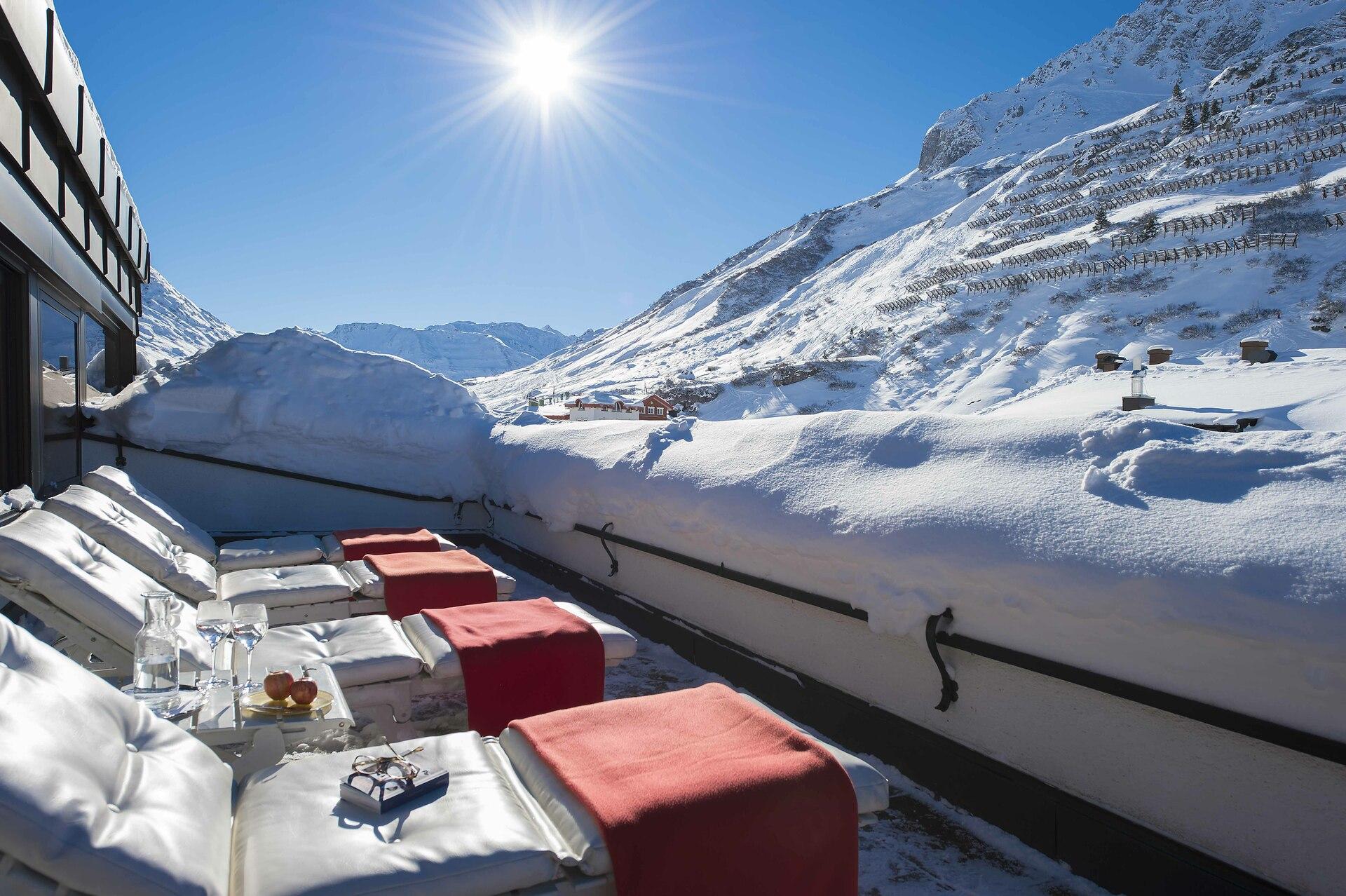 Dachterrasse des Hotels mit Ausblick auf die schneebedeckten Berge bei Sonnenschein