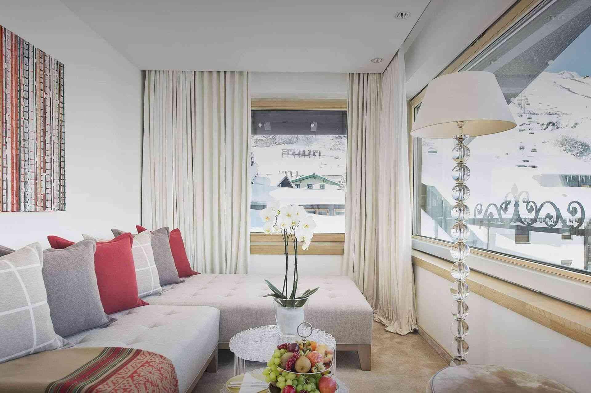 Eine gemütliche Couch, kleine Tische und eine Stehlampe vor einem Fenster