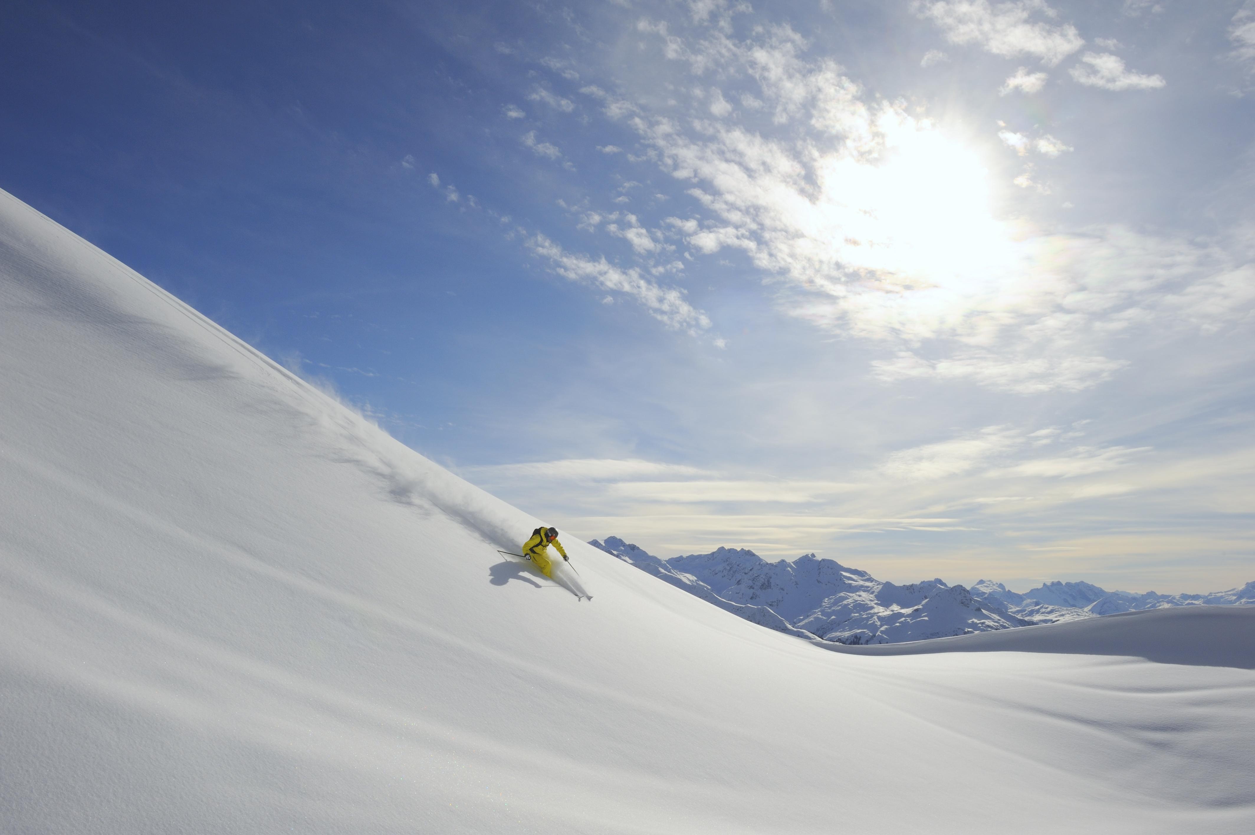 Ein Skifahrer fährt einen schneebedeckten Berg hinunter