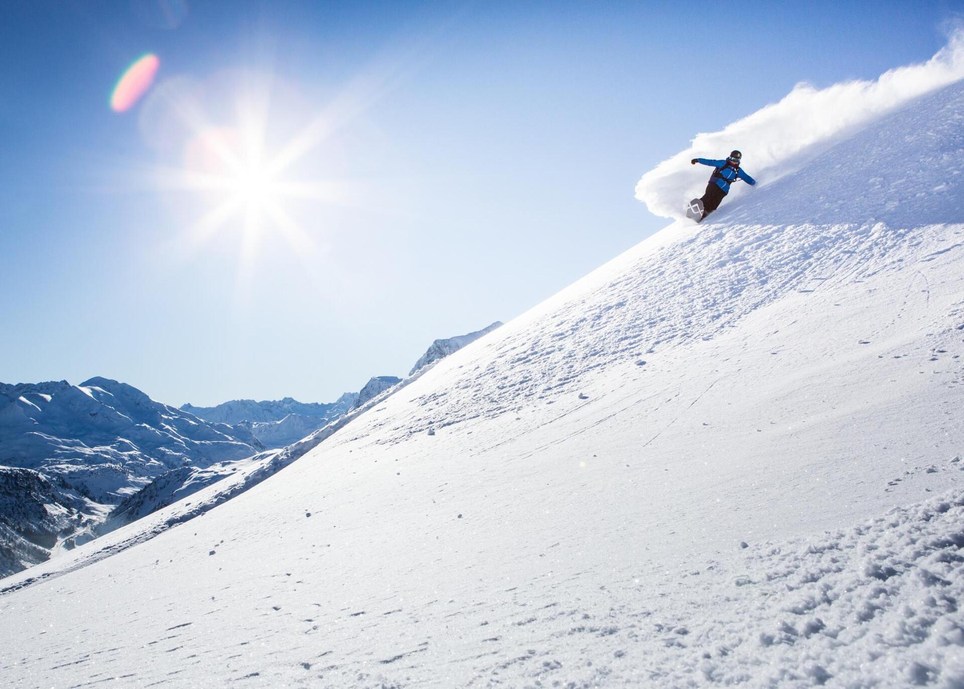 Ein Snowboardfahrer fährt einen schneebedeckten Berg entlang