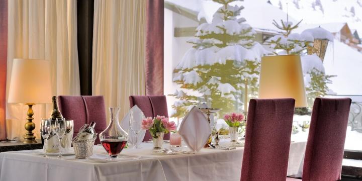 Festlich gedeckter Tisch im Restaurant Arlberg mit Blick auf die Schneelandschaft