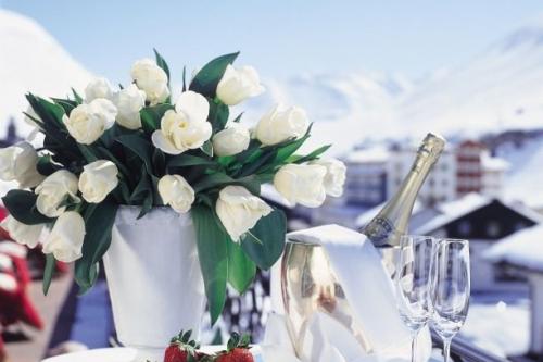 Blumenbouquet neben gekühltem Champagner und Sektgläsern