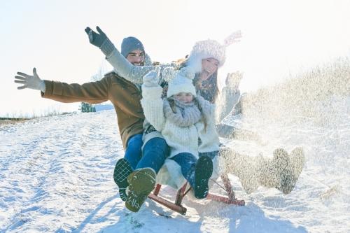 Eine dreiköpfige Familie fährt gemeinsam auf einem Schlitten