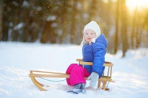 kleines Mädchen auf einem Schlitten im Schnee