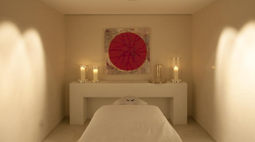 vorbereitete Massageliege mit Kerzen im Hintergrund