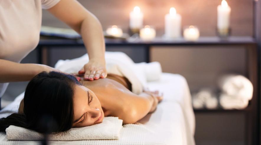 Eine Frau liegt entspannt auf dem Bauch und bekommt eine Massage