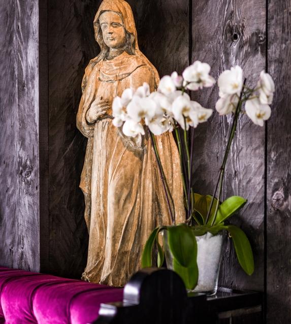 Madonna-Statue hinter einer Orchideenpflanze
