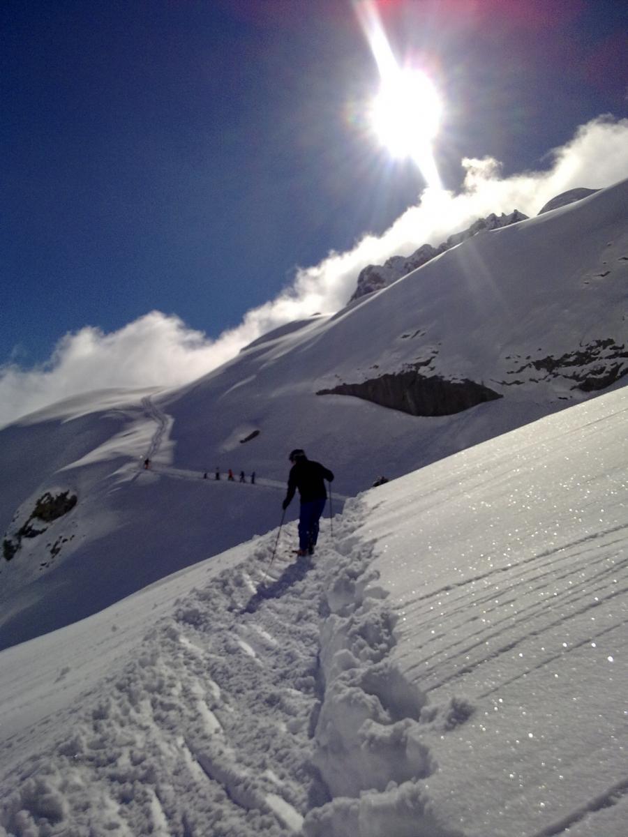 Skifahrer im unbefahrenen Tiefschnee entgegen der Sonne