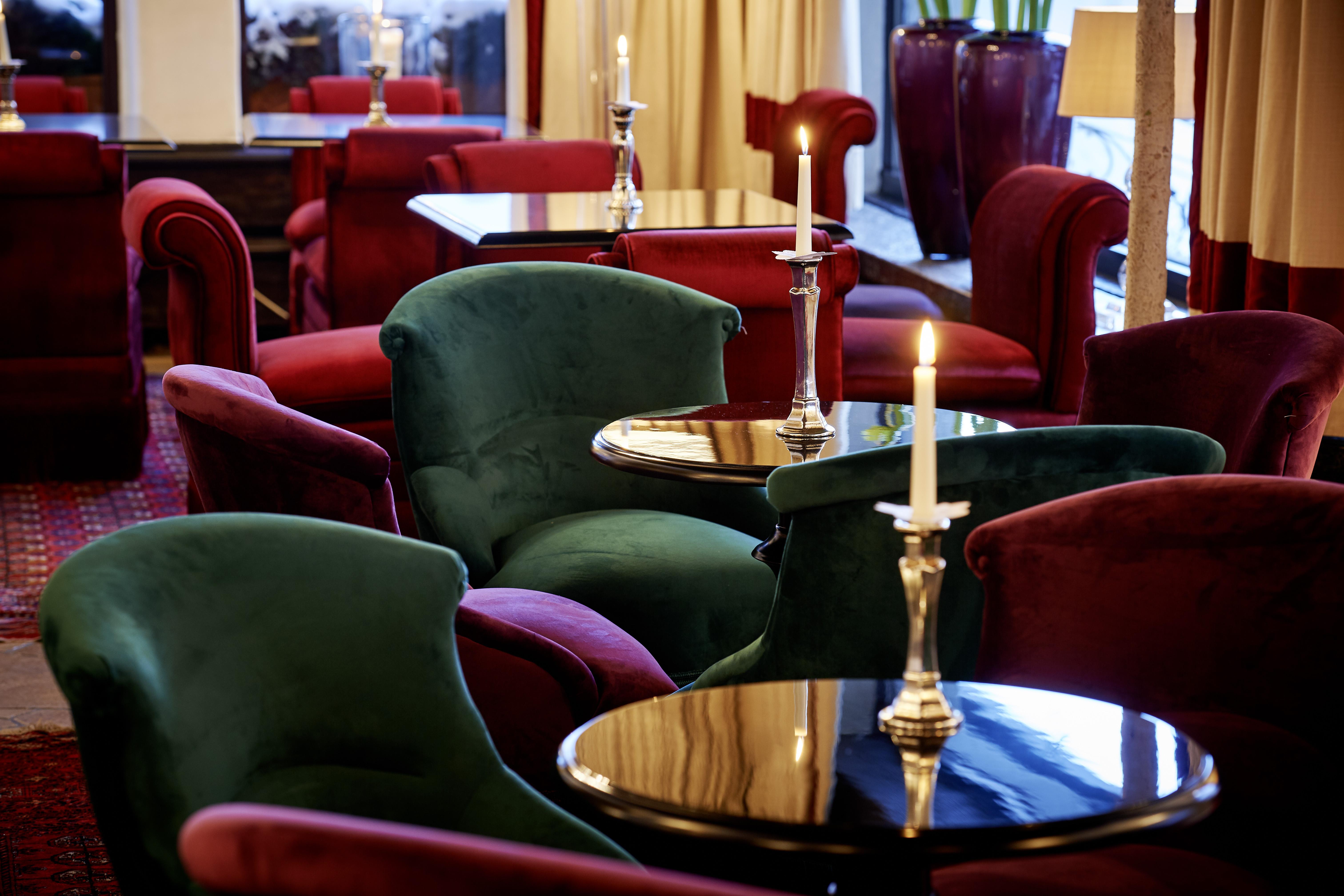 Stühle an kleinen Tischen mit Kerzenleuchtern in der Coco's Lounge des Hotels